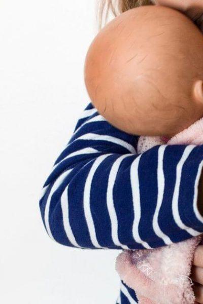 Toddler holding baby doll- newborn baby essentials